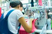 Asian Seamstress or worker in an Asian textile factory sewing with a industrial sewing machine, she