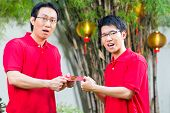 Father and grown up son celebrating Chinese new year with traditional gift, wearing red shirts