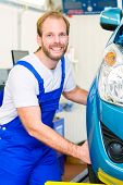 Mechanic in workshop or MOT with car or auto for service inspection