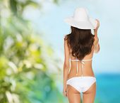 vacation, beauty and lingerie concept - back view of beautiful woman in white bikini and hat on a be