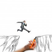 picture of gap  - Young businessman jumping over drawn mountain gap - JPG