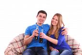 Young Couple Sitting On A Sofa And Drinking Coca Cola