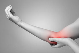 stock photo of elbow  - A young woman touching her painful elbow - JPG