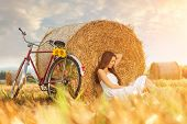 Fashion photo beautiful woman sitting in front of bales of wheat next to the old bike