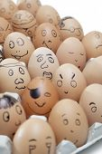 Various facial expressions painted on brown eggs arranged in carton