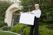 Portrait of a happy senior female agent hammering sign board in lawn