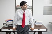 Indian businessman leaning on desk while looking away in office