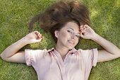 High angle portrait of beautiful young woman lying in grass