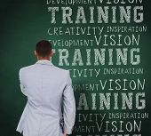 Thinking businessman against green chalkboard with business buzzwords
