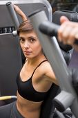 Serious brunette using weights machine for arms at the gym