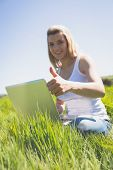 Pretty blonde sitting on grass using her laptop smiling at camera on a sunny day in the countryside