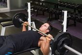 Determined young muscular man lifting barbell in gym