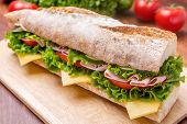 Long Baguette Sandwich with lettuce, slices of fresh tomatoes, ham, turkey breast and cheese cut in half