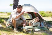 Outdoorsy couple cooking on camping stove outside tent on a sunny day