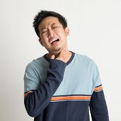 Asian male sore throat with painful face expression, on plain background