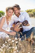 foto of serenade  - Handsome man serenading his girlfriend with guitar on a sunny day - JPG
