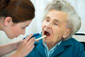 stock photo of pharyngitis  - Doctor examines elderly woman for sore throat - JPG