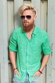 portrait of a fashion man in green shirt with long beard and sunglasses