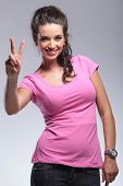 happy young casual woman making the victory peace sign in studio