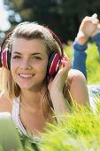 Pretty blonde lying on grass using laptop listening to music on a sunny day in the countryside