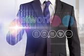 Businessman touching the word network on interface against abstract white line design in room