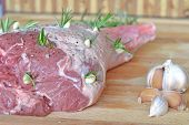 Fresh raw leg of lamb with rosemary and garlic