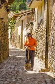 OLLANTAYTAMBO, PERU, MAY 4, 2014 - Local woman in hat carries a shovel in narrow ancient alley