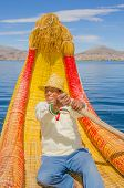 PUNO, PERU, MAY 5, 2014 - Local man in traditional attire rows sitting in reed boat (