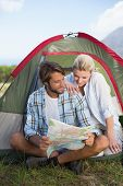 Attractive happy couple sitting by their tent reading map on a sunny day