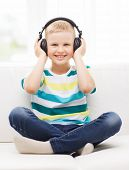 home, leisure, new technology, childhood and music concept - smiling little boy with headphones at h