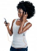 African woman with afro with headphones on listening to music from her phone isolated