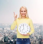 time, education and people concept - smiling young woman with wall clock showing 8 and finger up