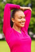 fitness, sport, training, park and lifestyle concept - smiling woman stretching leg outdoors