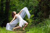 Artistic portrait of a beautiful barefoot woman in a stylish white dress striking a dramatic pose wi