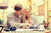 summer holidays, dating, city break and tourism concept - couple with map, camera, travellers guide