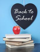 Back To School Heart Blackboard With Red Apple And Stack Of Books On Blue With Black Slate Table Bac