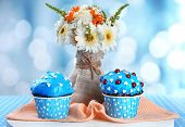 Tasty cupcake on table, on bright background