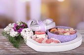 Present box with sweets and flowers on table on bright background