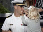 NEW YORK - MAY 23, 2014: US Navy Lt. Christopher Mikell's daughter fastens new shoulder boards to hi