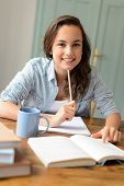 Student teenage girl studying at home sitting behind table smiling