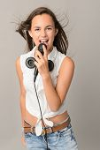 Beautiful teenage girl singing with microphone blowing hair on gray background