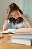 Student teenage girl concentrate reading book home holding her head