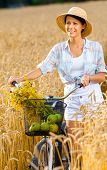 Woman pedals cycle with apples and flowers in rye field. Concept of rural lifestyle and sport