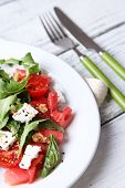 Salad with watermelon, feta, arugula and basil leaves on plate, on wooden background