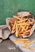 Tasty french fries in metal basket on table