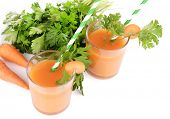 Glasses of carrot juice with fresh carrots and parsley isolated on white