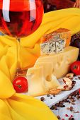 Different kinds of cheese with wine on table close-up