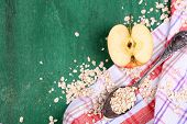 Apple with oatmeal and vintage spoons on napkin, on color wooden background