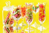 Different colorful fruit candy in glasses on yellow background
