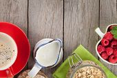 Healty breakfast with muesli, berries and milk. View from above on wooden table with copy space